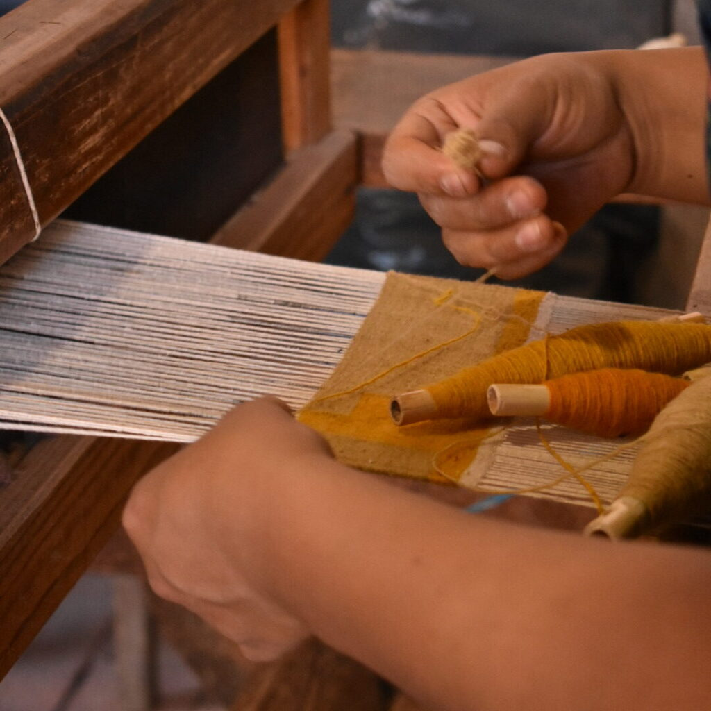 Close up of hands weaving a woollen rug at the loom