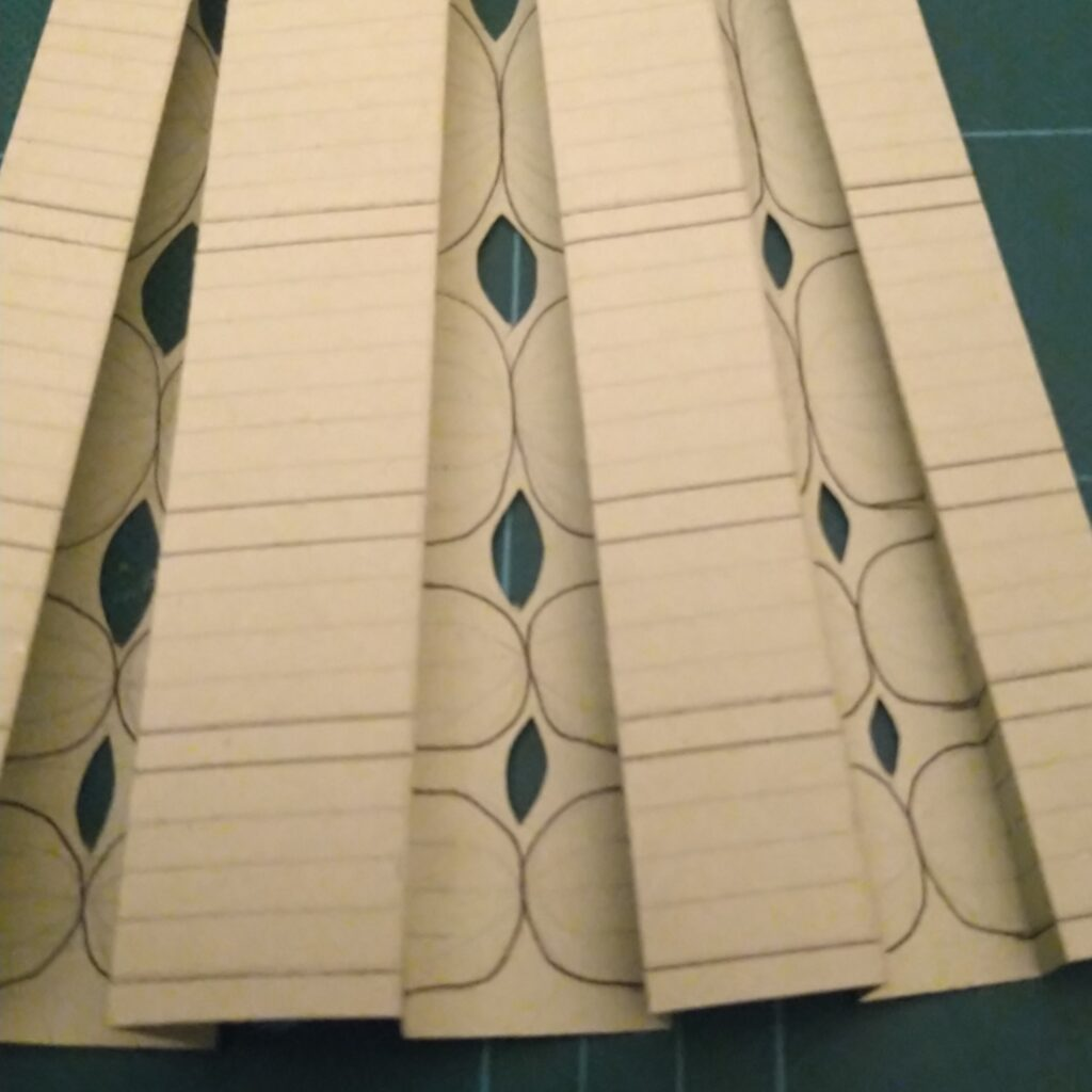 Exploring ancestral identity through kiltmaking - pleated paper model of handwoven fabric.